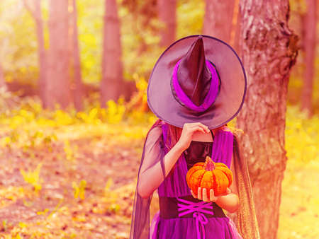 A girl in a Halloween costume with a hat over her eyes with orange pumpkin in the forest Фото со стока
