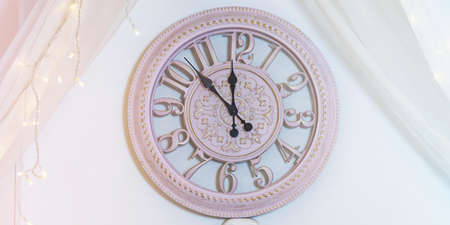The clock on the wall is pink. Five minutes left until the new year. Happy New Year.
