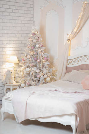 Christmas tree near the bed in the bedroom. New year and christmas concept.