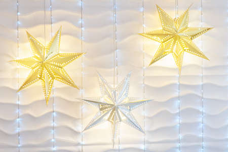 White wall christmas background with shiny lights. Wall with a garland. Фото со стока