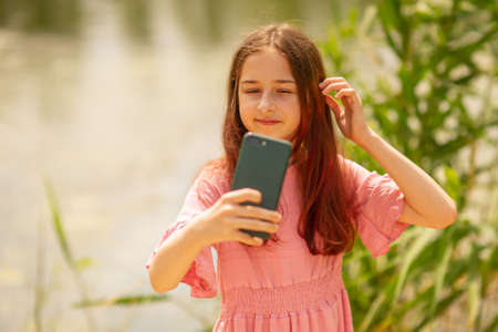 Portrait of a smiling young girl making selfie photo near the river in summer.