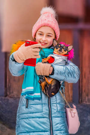 Happy smiling woman makes self portrait on smartphone in winter day. Teenager girl and chihuahua.