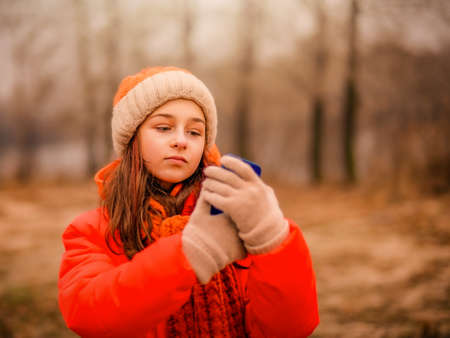 The girl is recording a video. Teenage girl looks into a smartphone in autumn or winter in the park.
