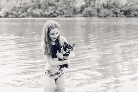 Teenage girl with a chihuahua dog by the river. Girl and chihuahua Фото со стока