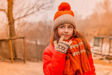 Portrait of little girl smiling wearing jacket, scarf and hat outdoor. Girl 10-11 years old.