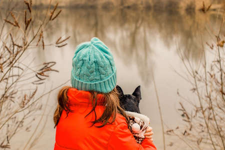 Owner and pet. Little girl in an orange jacket with a Chihuahua dog in nature back to the camera.