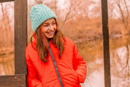 The smile of a child. Little happy girl laughing in nature in an orange jacket and hat. Фото со стока