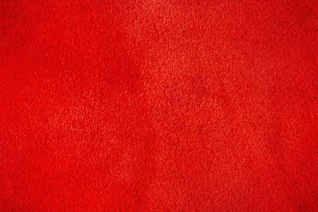 The texture is velvet red. Macro photo of red suede leather.