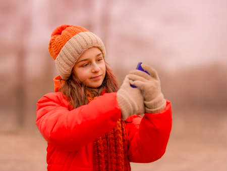 The girl takes a selfie. Teenage girl looks into a smartphone in autumn or winter in the park.