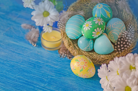 daisys: Easter eggs in the nest on rustic wooden background. Easter eggs and daisys on wooden planks Stock Photo