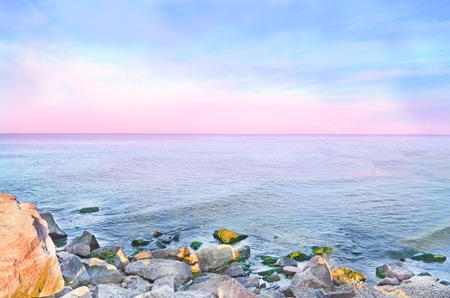 Sunset on the beach.  Pink horizon with first  sun rays.