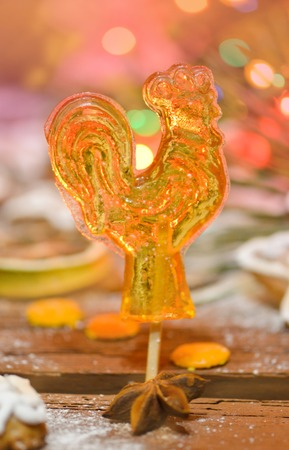 Sweet cock on wooden background. Candy lollipop cock. Vintage cock lollipops  Imagens