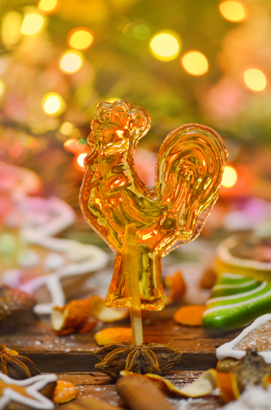 Sweet cock on wooden background. Sugar lollipop in the shape of rooster. Vintage cock lollipops  Stock Photo
