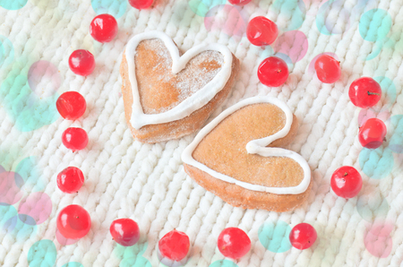 Love concept with red berries out in the form of heart  and  cookies in the form of heart  on a white tied background. Ripe red berries  and  cakes on a wooden background