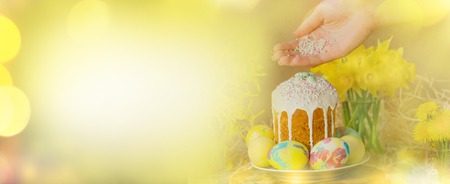 Easter banner background with copy space.  Girl with Easter eggs.  Spring flowers,  Easter cake and easter eggs. Easter colorful  banner.  Stock Photo