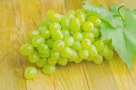 Bunch of grapes on wooden table. Grapes on wooden vintage table
