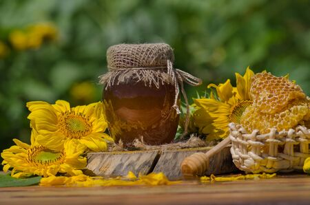 Honey with honey dipper on wooden table. Organic floral honey against blurred background with flowers 免版税图像