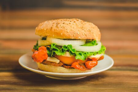 Close-up of home made burger. Burger with meat and cheese. Big delicious cheeseburger with bacon, cheese, lettuce and tomato. Space for text.