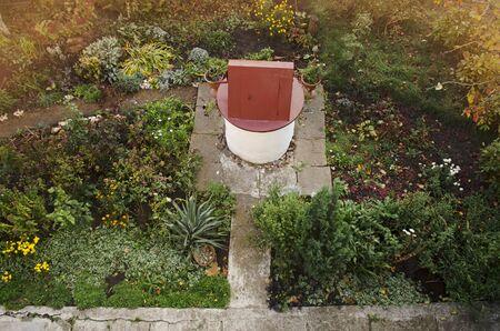 Garden landscape design. Stone well with drinking water in fall garden.