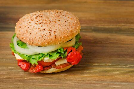 Preparation of delicious burger in a restaurant. Delicious burger on wood table background. Healthy chicken hamburger Archivio Fotografico