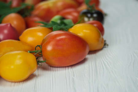Healthy organic vegetables on a wooden background. Fresh ripe organic garden tomatoes on wooden table.