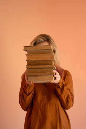 Portrait of a girl with a stack of books. Happy girl with pile book. Girl student holding in hands a pile of books.