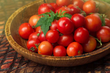 Little fresh tomatoes in a bowl. Cherry tomatoes in the bowl on dark wooden background