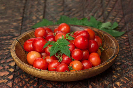 Little fresh tomatoes in a bowl. Cherry tomatoes in bowl on rustic table