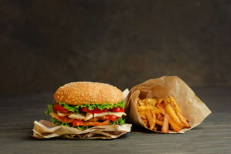 French fries and delicious and juicy burge in a rustic style