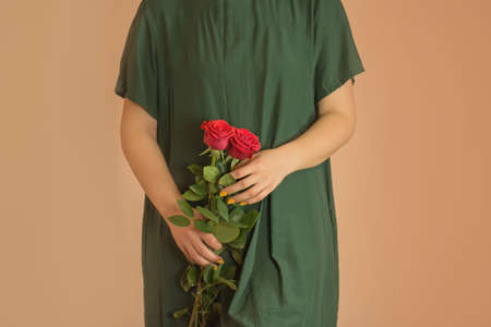 Young beautiful  girl in a strict modest, discreet, long green dress with red roses.  Girl with bouquet of red roses