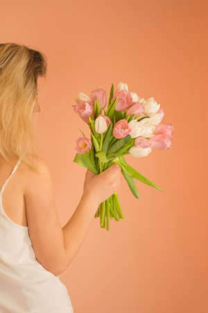 Young lovely girl in the white dress with colourful fresh flowers tulips