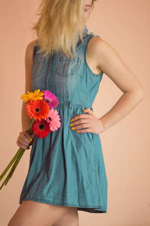 Young charming smile girl in casual jeans clothes. Young lovely girl in the denim dress with colourful fresh flowers gerberas