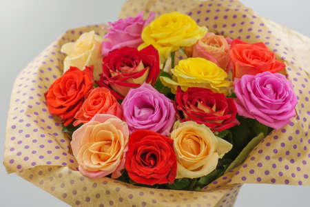 Bouquet of fresh beautiful flowers. Floral composition with roses. Delightful flowers on paper background