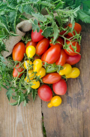 Tomatoes on wooden table. Fresh tomatoes on wooden table close up. Tomato on the old wood Stock Photo