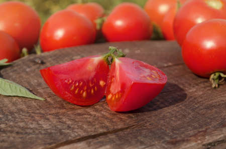 Tomato with slice on rustic wooden background. Fresh cut tomato on wooden table Stock Photo
