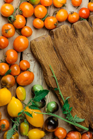 Beautiful ripe different varieties tomatoes on wooden background. View with copy space. Locally grown and sustainably harvested