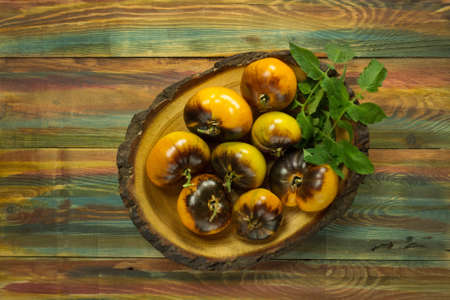 Homegrown yellow tomato in a wooden bowl. Raw yellow tomatoes ready to eat. Yellow tomatoes Blue Gold on wooden background.