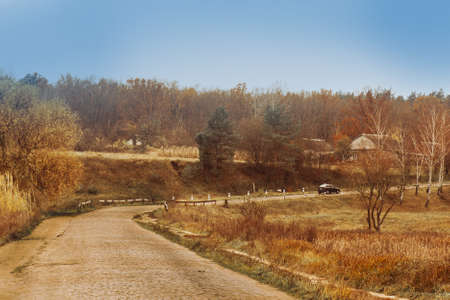 Colorful autumn landscape in the village. Beautiful sunset in farmland near the road. Village in autumn