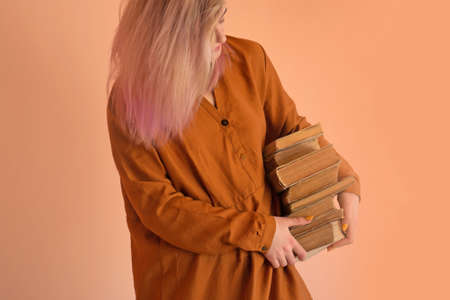 Happy casual girl holding stack color book. Student standing with books. Portrait of a girl with a stack of books