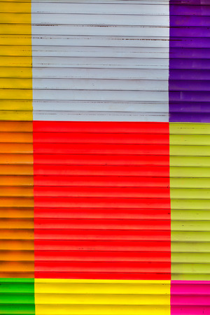 Digital background for studio photographers . Painted corrugated metal roller shutter door with colorful paint squares photo
