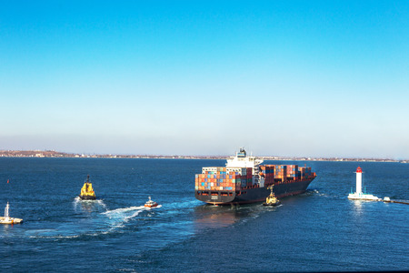 allegedly: ODESSA, UKRAINE - NOVEMBER 24: Marine cargo ship loaded with shipping containers Ukrainian industrial goods coming out of harbor seaport. Vorontsov Lighthouse , November 24, 2011 Odessa, Ukraine Editorial