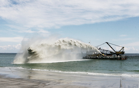 Dredging panning sand on the beach during the construction of a new sea freight terminal in the harbor of Port photo