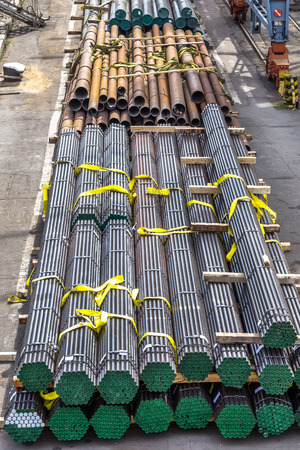 deconstruct: A pile of round and square metal pipes, chocks , packed in stacks with tags size parameters for cranes and transport of cargo ships in the seaport and railway wagons