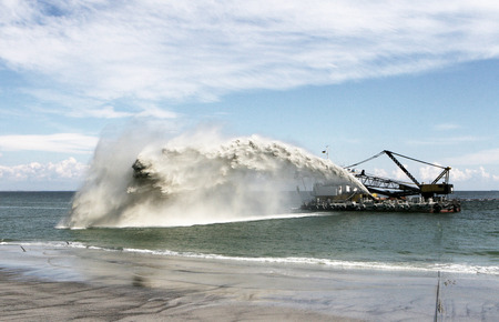 Dredging , panning sand on the beach during the construction of a new sea freight terminal in the harbor of Port Standard-Bild