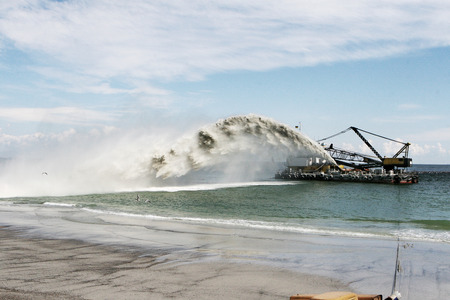 Dredging , panning sand on the beach during the construction of a new sea freight terminal in the harbor of Port Stock Photo