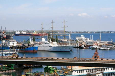 allegedly: ODESSA, UKRAINE - APRIL 15  maritime cargo ships and sailboat moored in the harbor of Odessa sea port   Landscape view of the Bread harbor port , April 15, 2014 Odessa, Ukraine