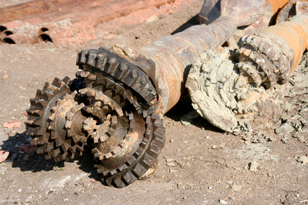 caked: Rusty old drilling bit caked with mud and dirt Stock Photo