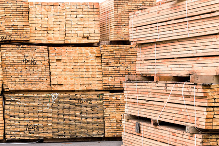 A pile of wood edged boards packed in stacks with tags size parameters for loading cranes and transport the cargo ships in the seaport  photo