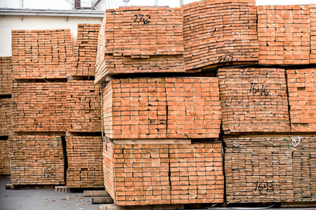 primary product: A pile of wood edged boards packed in stacks with tags size parameters for loading cranes and transport the cargo ships in the seaport