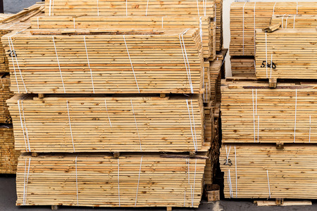 A pile of wood edged boards packed in stacks with tags size parameters for loading cranes and transport the cargo ships in the seaport and railway wagons  photo